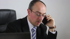 Businessman at work speaking on cell phone - stock footage
