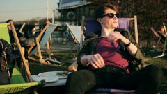 Student lying on sunbed and relaxing in outdoor bar Stock Footage