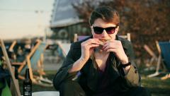 Student sitting on sunbed and eating pizza outside the bar - stock footage