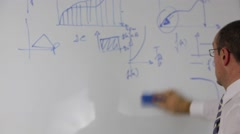 Man in shirt and tie erasing a whiteboard - stock footage