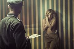 Frightened lady during the interrogation - stock photo