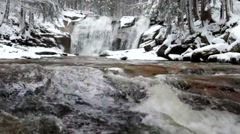 Foamy rapid stream into cascade of waterfal.  Stream in deep freeze. - stock footage