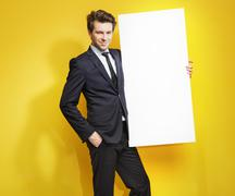 Handsome gentleman carrying white board - stock photo