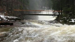 Huge stream of rushing water masses below small footbridge with peaope. - stock footage