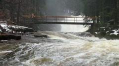 Huge stream of rushing water masses below small footbridge with peaople. Stock Footage