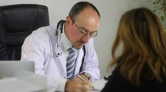 A doctor is explaining a prescription to a patient - stock footage