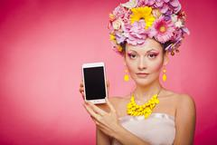 Smartphone app demonstration by woman in flowers Stock Photos