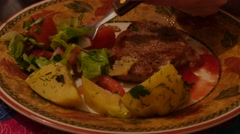 Close up of pork chop with vegetables and potato in the eating process Stock Footage