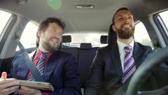 Two happy business men laughing driving car working - stock footage