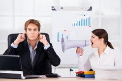 Businesswoman screaming with megaphone on boss Stock Photos