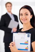 Businesswoman holding folders with diagrams Stock Photos