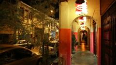 Penang night arches, Chinese lanterns, man walks in street Stock Footage