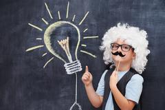Portrait of male elementary school student in Einstein costume Stock Photos
