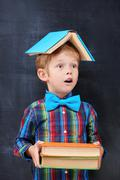 Mixed-up ginger school-boy overloaded with books - stock photo
