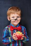 Mixed-up ginger primary school age boy holding red apple - stock photo
