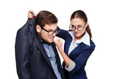 Strict female boss holding afraid businessman by collar - stock photo