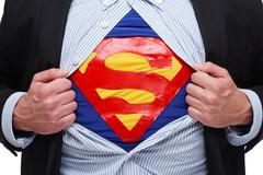 Close up of businessman with superman costume under his shirt - stock photo