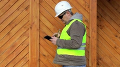 Engineer with tape measure and tablet PC near wooden building Stock Footage