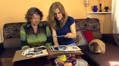 Granny watch black white old photo album with her granddaughter Stock Footage