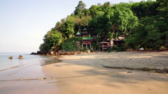 Thai island wooden holiday huts on jungle hillside with beach long shot Stock Footage