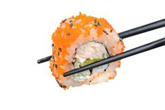 Sushi roll with black chopsticks - stock photo