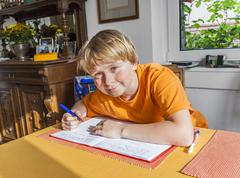 Cute pupil writes in a book and prepares homework Stock Photos