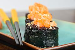 Baked sushi rolls served on turquoise plate - stock photo