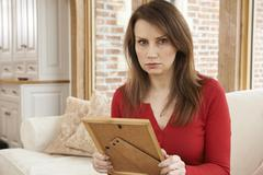 Unhappy Mature Woman Looking At Photograph In Frame Stock Photos