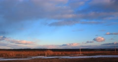Sunset clouds 4k time lapse moving through farm land and forest Stock Footage