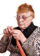 The old woman is engaged in knitting - stock photo