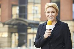 Female Journalist Broadcasting Outside Office Building Stock Photos