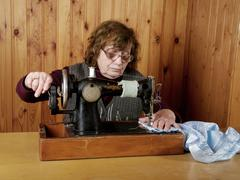 The old woman sews on the sewing machine Stock Photos