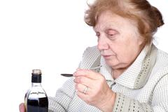 The old woman pours a liquid - stock photo