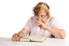 The old woman in points thoughtfully looks in the book - stock photo