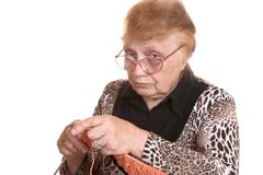 The old woman is engaged in knittin Stock Photos