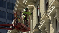 Man on cherry picker window cleaner, building, Wellington, New Zealand Stock Footage