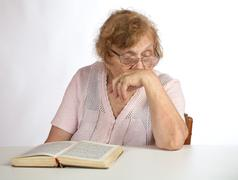 old woman in glasses reads the book - stock photo