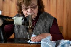 The old woman sews - stock photo
