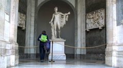 Tourist girl examines the Apollo Belvedere sculpture Stock Footage