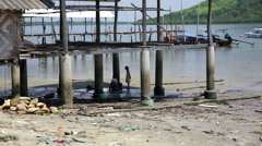Children playing under pier, traditional fishing village Stock Footage