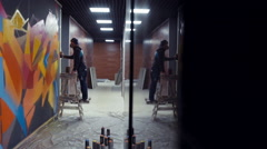 Graffiti artist painting on the wall with reflection in the column, interior Stock Footage