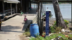 Tsunami hazard sign, entrance to on stilts house with lagoon in background, fish Stock Footage