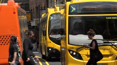 People cross road in front of Go trolley buses, Wellington, New Zealand Stock Footage