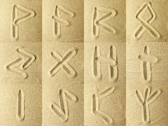 runes Written in the Sand - stock photo