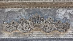 Balinese temple wall with traditional guard demon head Stock Photos