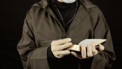 Friar reading holy book end Stock Footage
