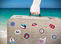 Hand holds a suitcase with stickers Stock Photos