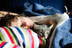 Woman sleeping with cat - stock photo