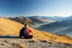 Hiker resting on the mountain top Stock Photos