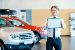 Young smiling salesman with clipboard in car dealership - stock photo